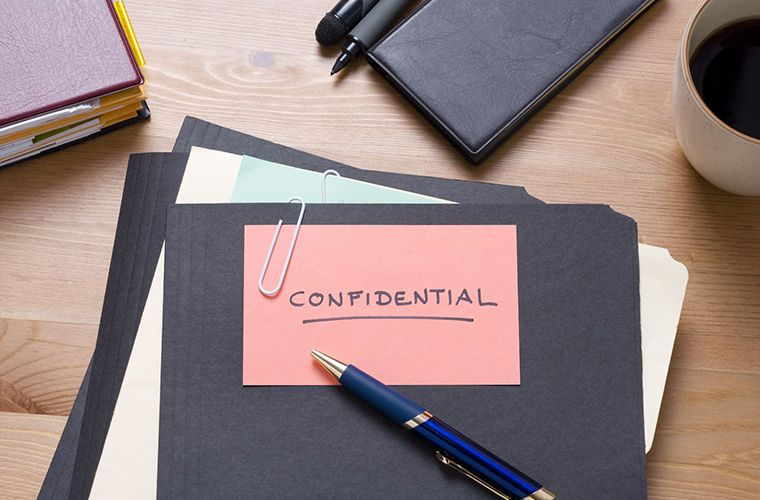 Confidential documents on a wooden table