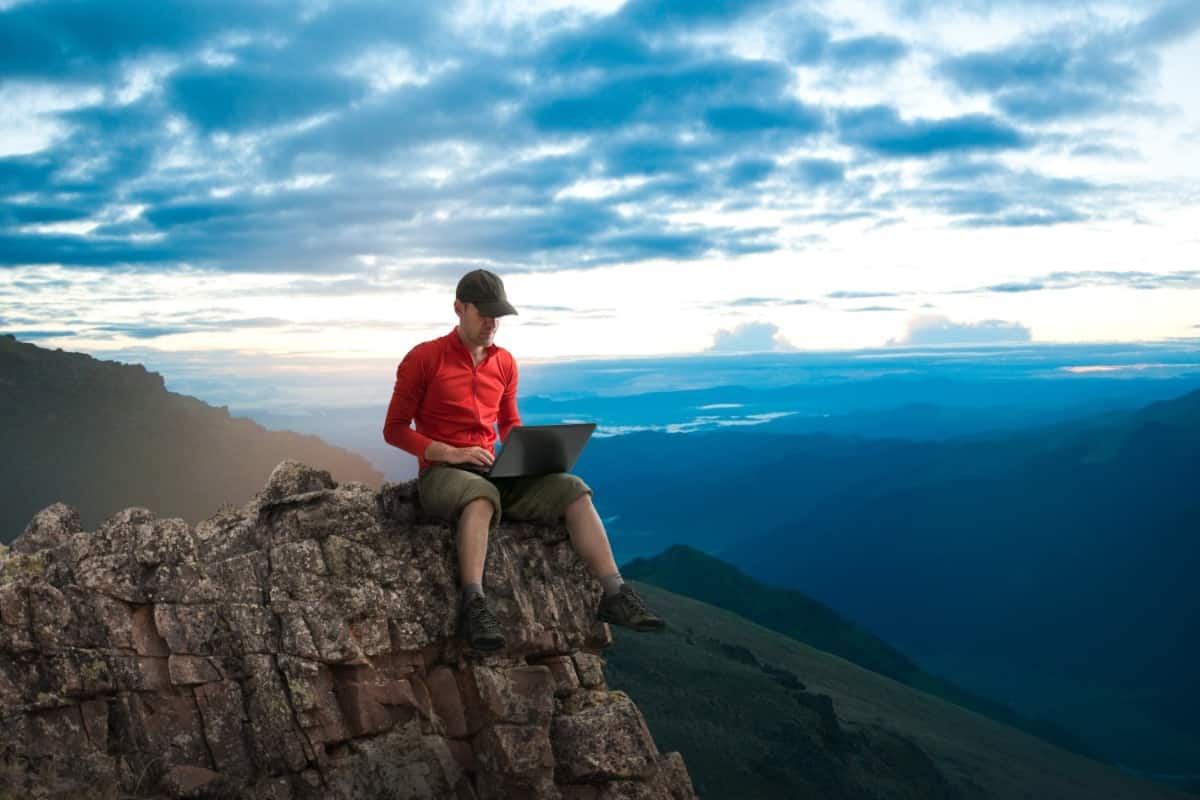 Man sitting on a top of a mountain with a laptop