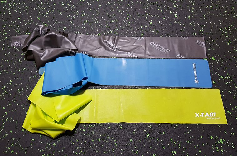 Three resistance bands displayed on the floor