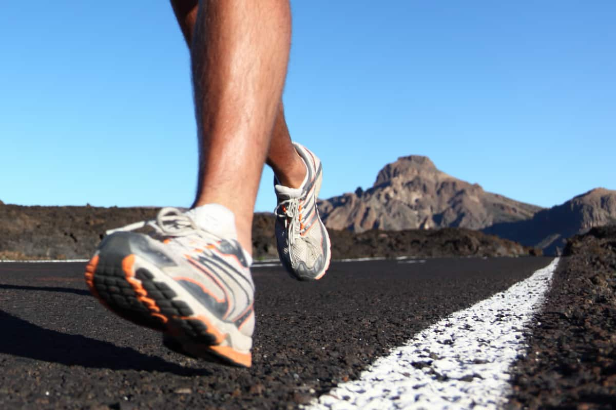 Running sport shoes closeup outdoors in action on mountain road.