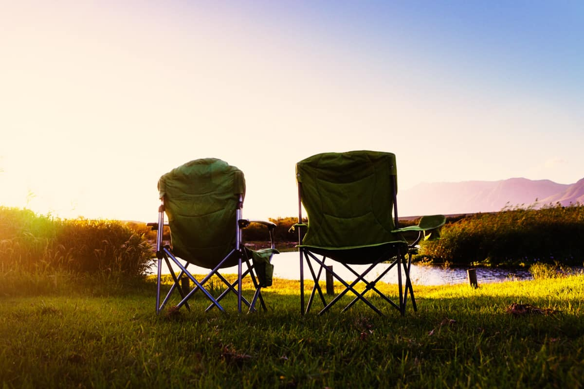 Two camping chairs by sunlit river at dusk