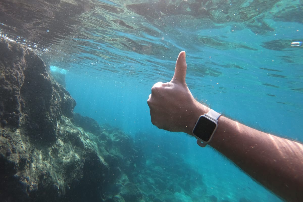 Close up of a hand with a waterproof smart watch underwater in the sea.