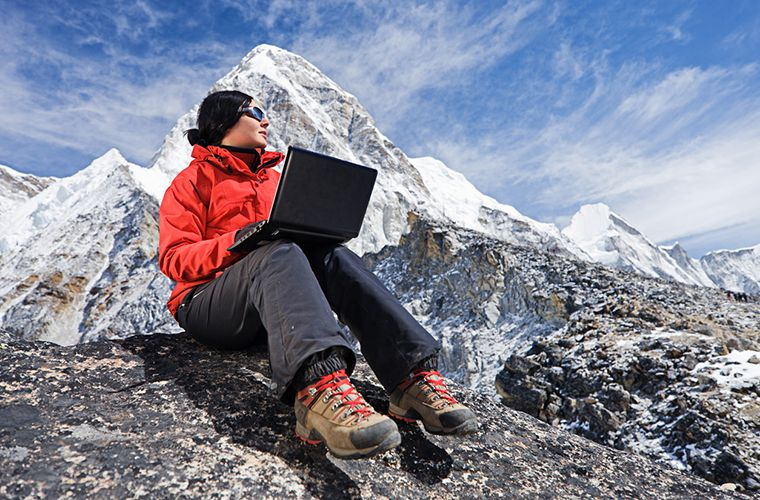 woman sitting on a mointain with a rugged laptop