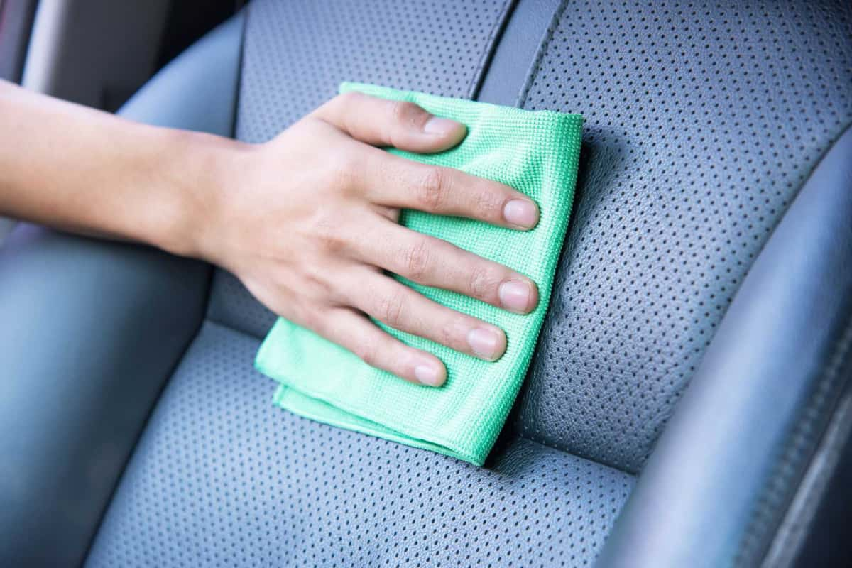 Woman cleans a leather car seat