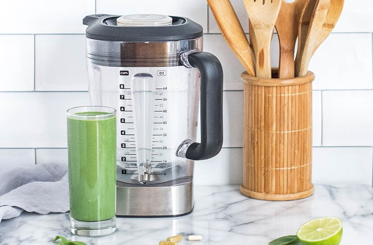 green smoothie next to a blender on a kitchen counter top