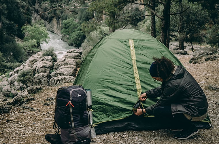 woman setting up a tent in the wilderness