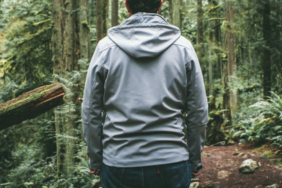 man standing in the woods with a gray hoodie