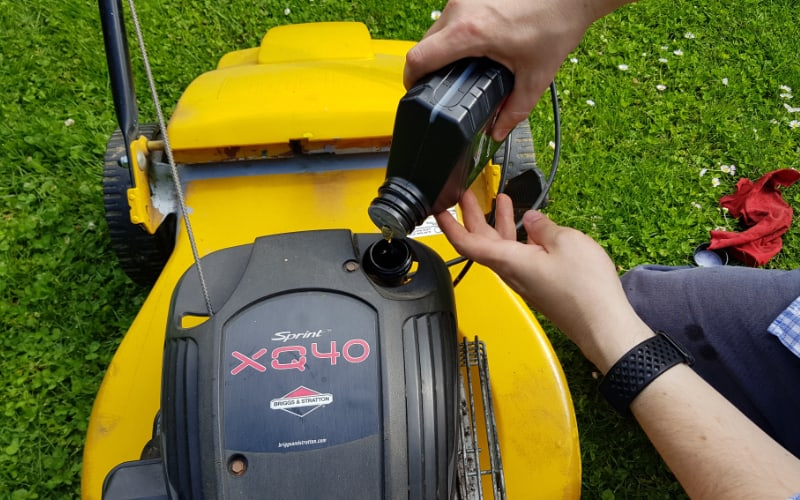 adding oil to a lawn mower