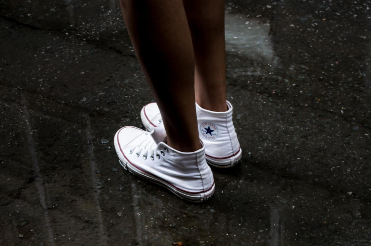 woman standing in water wearing white converse