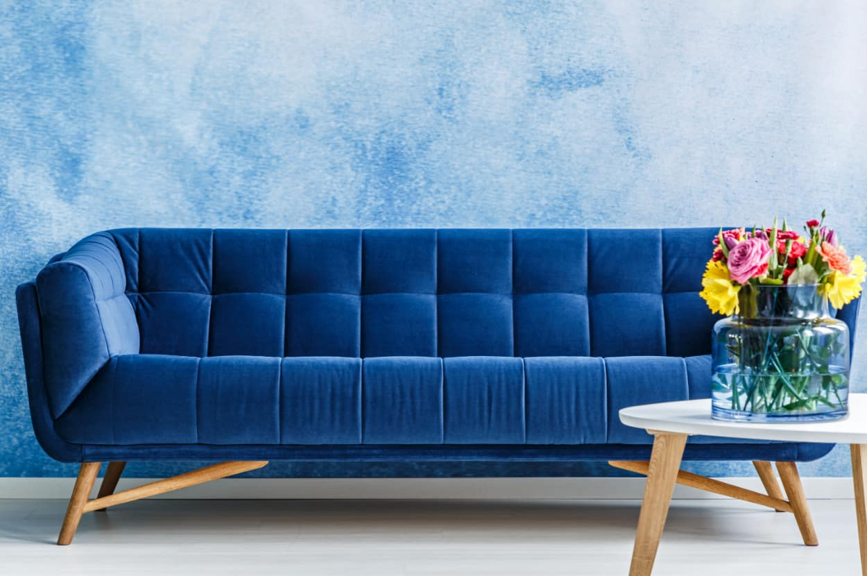 Flowers on white wooden table next to navy blue suede couch